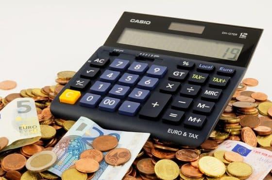 Schwarzer Taschenrechner liegt auf Münzen und Euro Scheinen