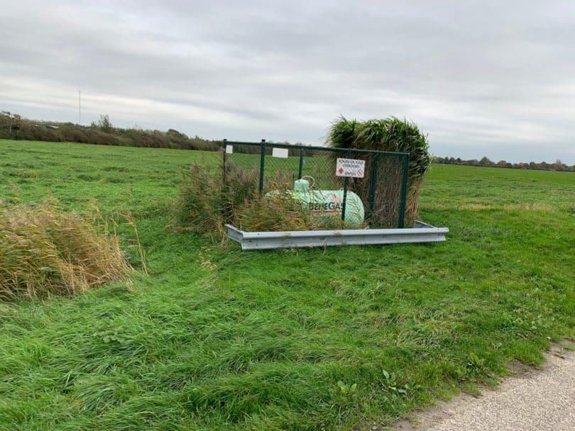 Eingezäunter grüner Flüssiggastank 990 Liter oberirdisch auf einer Wiese