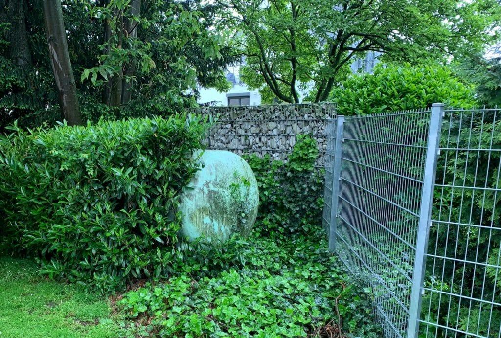 Fluessiggastank oberirdisch hinter Pflanzen mit Zuwegung