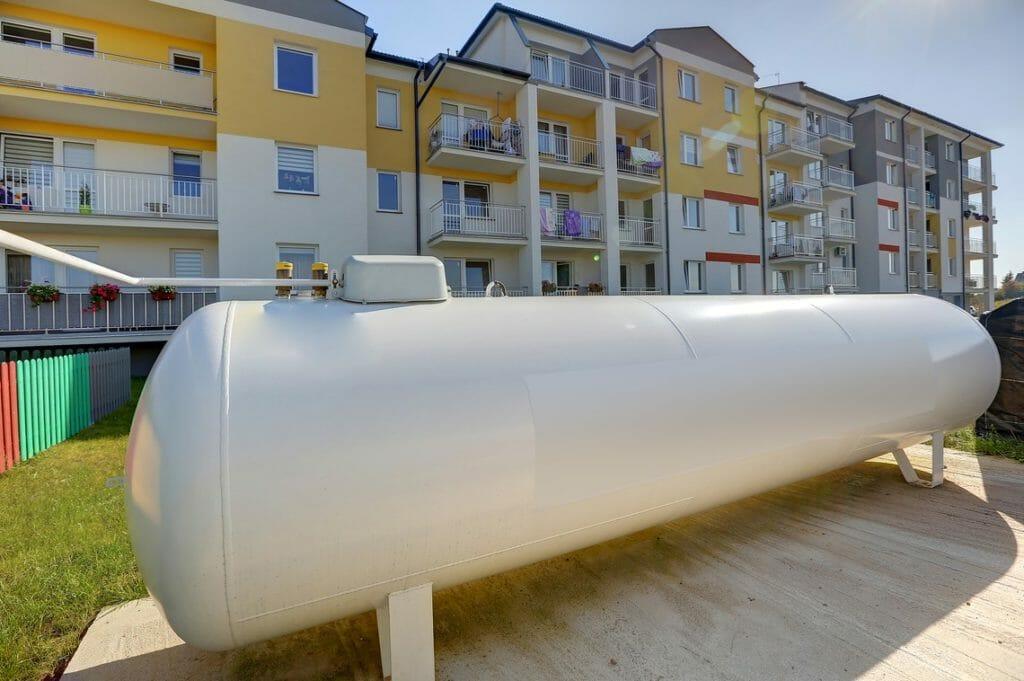 Weißer Flüssiggastank vor Mehrfamilienhaus